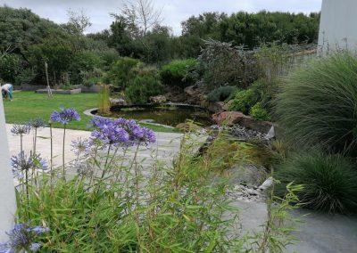 Allée pavée, jardin aménagé et bassin
